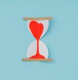 Coupe de papier des coeurs dans l'horloge de sable Photos libres de droits