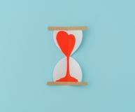 Coupe de papier des coeurs dans l'horloge de sable Photos stock