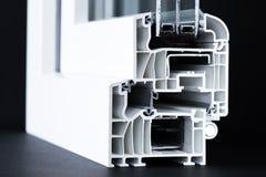 Coupe de plan rapproché de profil de fenêtre de PVC, glaçage triple, fond noir images stock