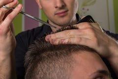 Coupe des cheveux des hommes avec des ciseaux dans un salon de beauté image libre de droits