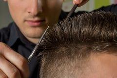 Coupe des cheveux des hommes avec des ciseaux dans un salon de beauté image stock