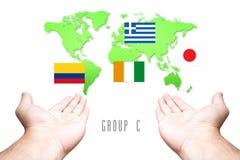 Coupe du monde drapeau de 2014 groupes-c avec le fond de carte de main et du monde Photographie stock