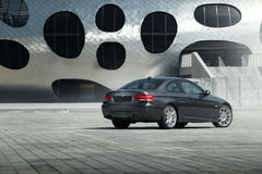 Coupe E92 BMW автомобиля стоя на месте для стоянки sett пустом около современного здания на дневном времени Стоковые Фотографии RF