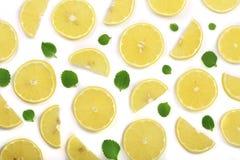 Coupe en tranches le citron avec les feuilles en bon état d'isolement sur le fond blanc Configuration plate, vue supérieure Photos libres de droits