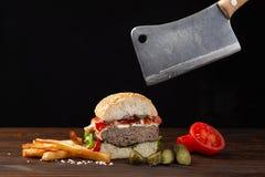 Coupe faite maison d'hamburger en demi plan rapproch? avec du boeuf, la tomate, la laitue, le fromage et les pommes frites sur la photos libres de droits