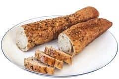 Coupe intégrale de pain de baguette dans les tranches du plat blanc - d'isolement Image libre de droits