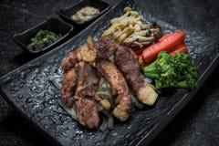 Coupe japonaise grillée de nourriture de viande sur le service de plat noir avec des légumes Photographie stock libre de droits