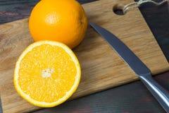 Coupe juteuse d'orange dans la moitié pour faire le jus d'orange pour le petit déjeuner Photos libres de droits