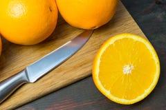 Coupe juteuse d'orange dans la moitié pour faire le jus d'orange pour le petit déjeuner Images libres de droits