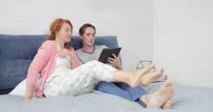 Coupe Lying On Bed Using Digital Tablet Computer, Man And Woman Talking In Bedroom Browsing Internet. Slow Motion 60 stock video