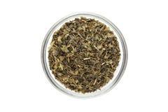 Coupe organique de sachet à thé de thé vert (sinensis de camélia), feuilles sèches, dans le bol en verre Images stock