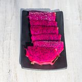 Coupe rose exotique de fruit du dragon sur la fin de fond  Photo de texture de Pitahaya Fruit tropical doux, coupe juteuse de pit Photos libres de droits