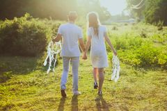 Coupe With White Dress and Suit Holding a White Dreamcatcher While Walking on Green Grass Stock Photography