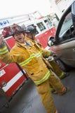 Couper de sapeurs-pompiers ouvrent un véhicule images stock