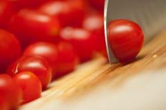 Couper en tranches des tomates-cerises Photographie stock