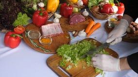 Couper en tranches la laitue part sur une planche à découper, pour faire cuire un plat, laitue, se préparant à la cuisson La cuis banque de vidéos