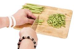 Couper en tranches les haricots verts frais sur une planche à découper sur une table images libres de droits