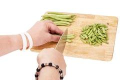 Couper en tranches les haricots verts frais sur une planche à découper sur une table photo stock