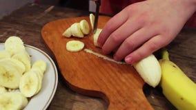 Couper en tranches une banane dans les tranches minces banque de vidéos