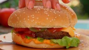Coupes de couteau en moitié d'un hamburger délicieux banque de vidéos