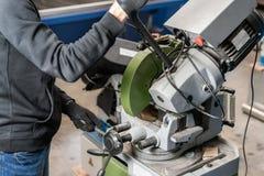 Coupes de travailleur par morceau avec une machine circulaire de scie Ingénieur industriel travaillant à couper un métal et un ac photo stock