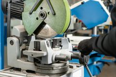 Coupes de travailleur par morceau avec une machine circulaire de scie Ingénieur industriel travaillant à couper un métal et un ac images stock