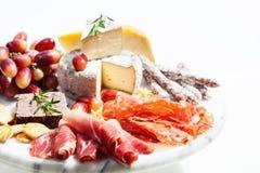 Coupes froides, fromage et raisins sur le plateau image libre de droits