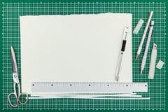 Coupeur avec des lames, des ciseaux, le crayon, la règle et le shee de papier vide Photos libres de droits