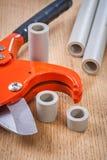 Coupeur de tuyau et tuyaux cutted sur la composition en conseil en bois Image stock