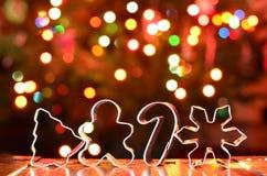 Coupeurs argentés de biscuit de Noël avec le fond coloré de bokeh Photos stock