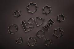 Coupeurs de biscuit formés par amour sur le fond noir Photo stock