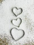 Coupeurs en forme de coeur de pâtisserie au-dessus d'une pâte - verticale Images libres de droits