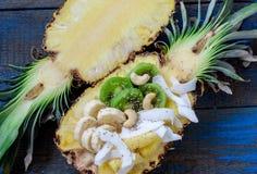 Coupez en demi ananas avec la noix de coco, chia, kiwi, anarcadier Images libres de droits