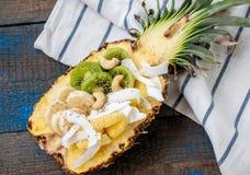 Coupez en demi ananas avec la noix de coco, chia, kiwi, anarcadier Image stock