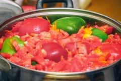 Coupez en morceaux les l?gumes - paprikas, tomates, etc. - dans une casserole brillante en m?tal sur la table de cuisine photographie stock libre de droits