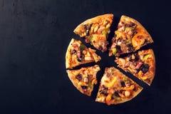 Coupez en tranches délicieuses la pizza fraîche avec des champignons et des pepperoni sur un fond foncé Vue supérieure Pizza sur  Photo libre de droits