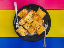 Coupez en tranches le pain croustillant dans le plat en céramique noir pour mangent sur l'étiquette colorée image stock