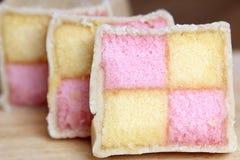 Coupez fraîchement les tranches de gâteau de Battenberg avec l'éponge rose et jaune couverte en massepain Image libre de droits