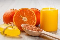 Coupez l'orange avec deux oranges entières, le savon, cuillère en bois avec le yello Photographie stock libre de droits