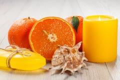 Coupez l'orange avec deux oranges entières, savon, coquille de mer et c brûlant Photos stock