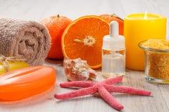 Coupez l'orange avec deux oranges entières, serviette, savon, coquille de mer, starf Photographie stock libre de droits