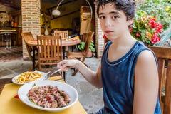 Coupez la viande et les pommes chips pour un garçon Photographie stock