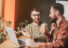 Coupez la vue des types reposant et ayant une conversation Sur de eux dranking le café tandis qu'un autre explique quelque chose Images libres de droits