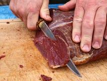 Coupez le boeuf rôti de viande par un chef Photos stock