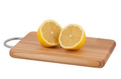Coupez le citron sur le panneau de découpage. Image libre de droits