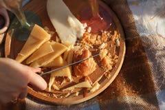 Coupez le fromage du plat en bois photographie stock
