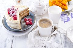 Coupez le gâteau avec de la crème blanche, pour le fruit de mangue du petit déjeuner A Fond blanc, nappe avec la dentelle, une ta image libre de droits