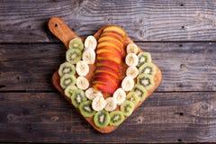 Coupez le kiwi, la banane et la nectarine se trouvant sur une planche à découper Photographie stock libre de droits