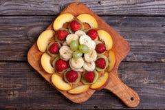 Coupez le kiwi, la banane et la nectarine se trouvant sur une planche à découper Photos libres de droits