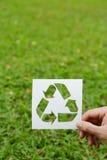 Coupez le papier avec le logo de la réutilisation au-dessus de l'herbe verte Photographie stock